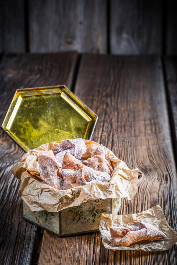 Angel wings with sugar powder in box. On old wooden table royalty free stock photos
