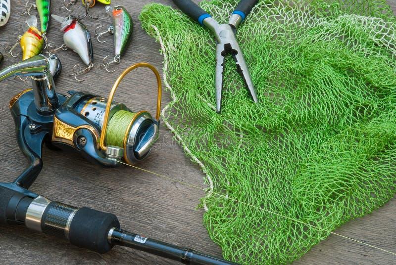 Angelausrüstung - das Fischenspinnen, -haken und -köder verdunkeln an hölzernen Hintergrund stockfotografie