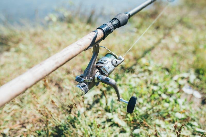 Angelausrüstung - Fischenspinnen, -haken und -köder auf dem Sonnenschein im Freien stockfotos