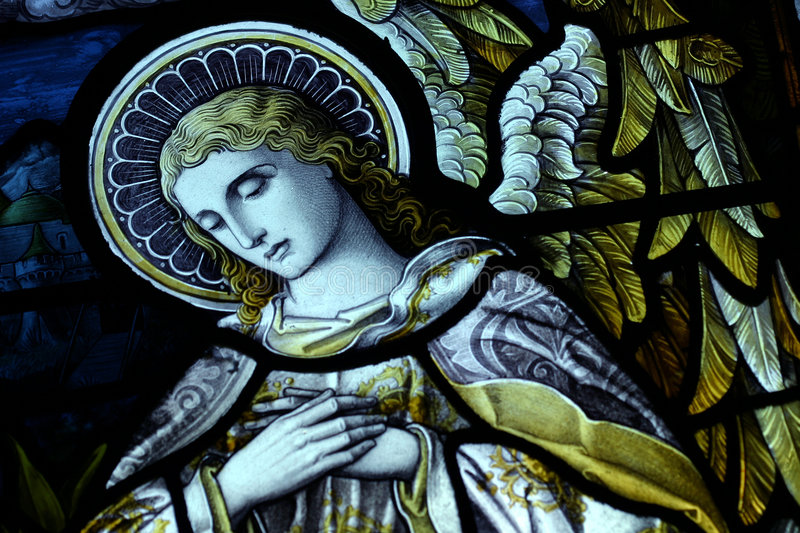 Angelic. The face of an angle in a broken stain glass window stock photo