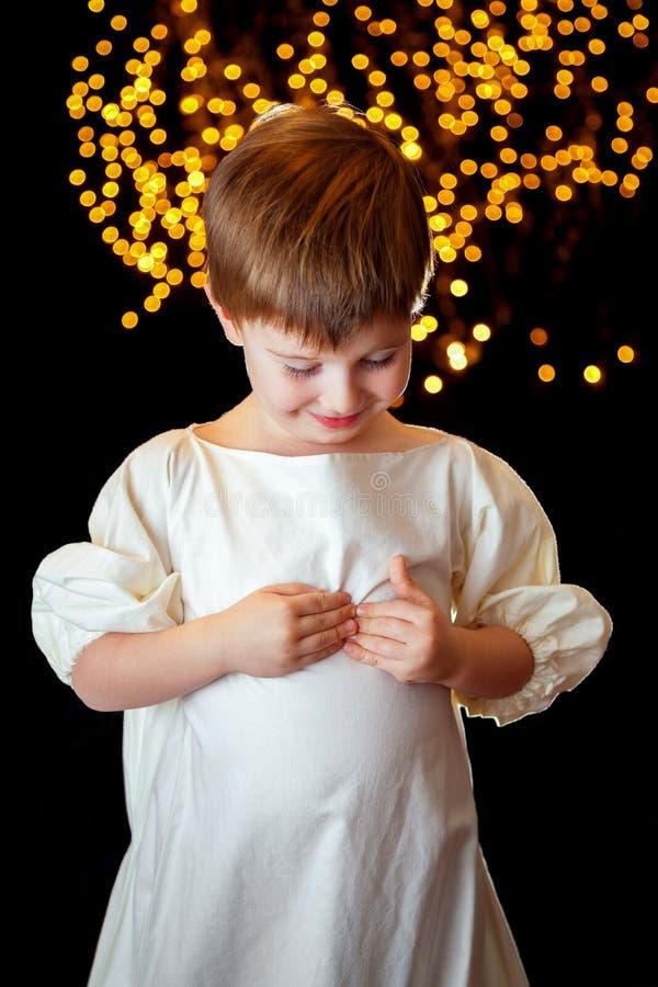 Angelic Boy Looking Down Holding Zijn Hart royalty-vrije stock afbeelding