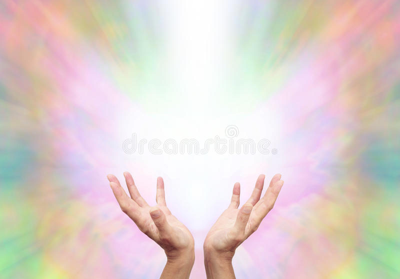 Angelic Energy Healer. Female energy worker with hands outstretched and open upwards sensing healing energy on ethereal rainbow colored energy formation stock photography