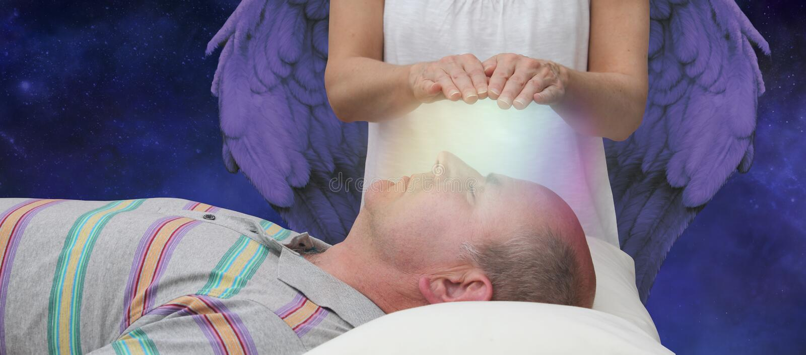 Angelic help during a healing session. Female hands hoovering above a male patient& x27;s face channeling energy together with a higher power in the background royalty free stock photo