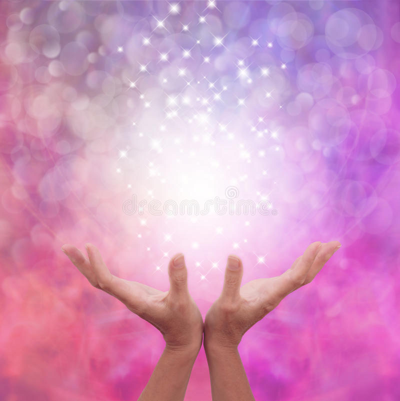 Angelic Pink Healing Energy. Female hands open flat on a pink bokeh background with a ball of white light and sparkles floating above stock image