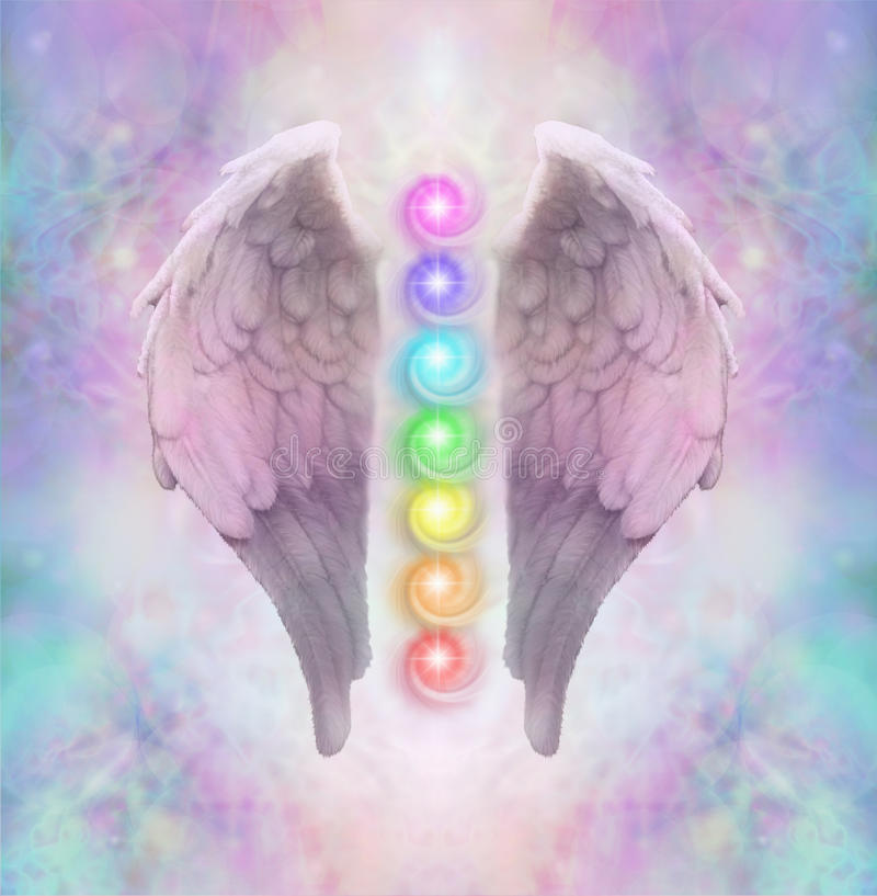 Angelic Sacred Chakras. Angel wings with seven chakras floating between an ethereal pastel colored delicate energy background royalty free stock photo