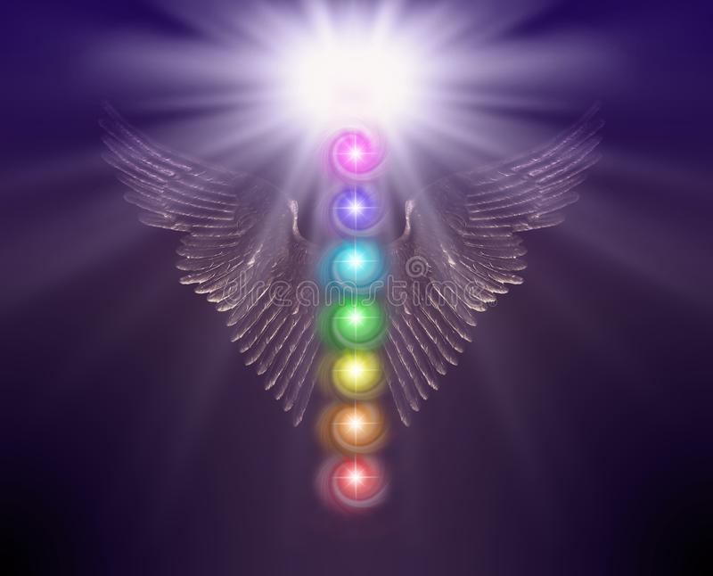 Angelic Sacred Healing Chakras Background. Golden shimmering Angel wings with bright white orb above and seven chakras floating between against a dark coloured royalty free stock photo