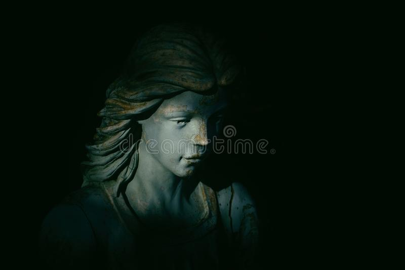 Angelic Statue. In spiritual light with black copy space. Low key image royalty free stock image