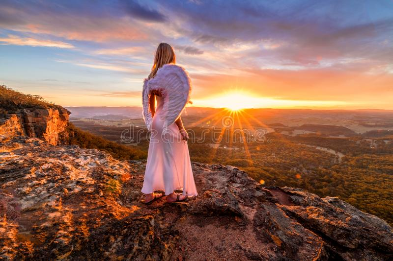 Angelic woman with angel wings and white dress on mountain cliffs sunset royalty free stock photography