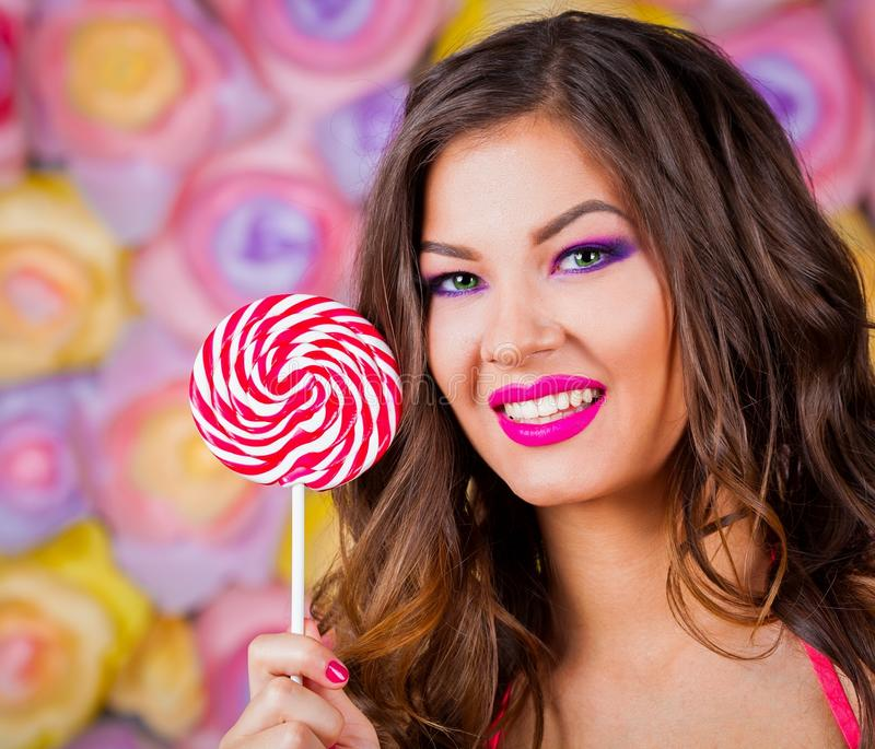 Angelica, face lollipop pink background green contact lenses. Beautiful amazing lady smiling joy fun woman. Face haired green contact lenses eyes. Studio royalty free stock image