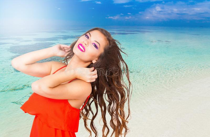 Angelica. red dress sea!. Portrait pretty fun joy smiling brunette woman, has red dress, tan face and body, pink lips makeup. Sun tropical hot blue sea water royalty free stock photos