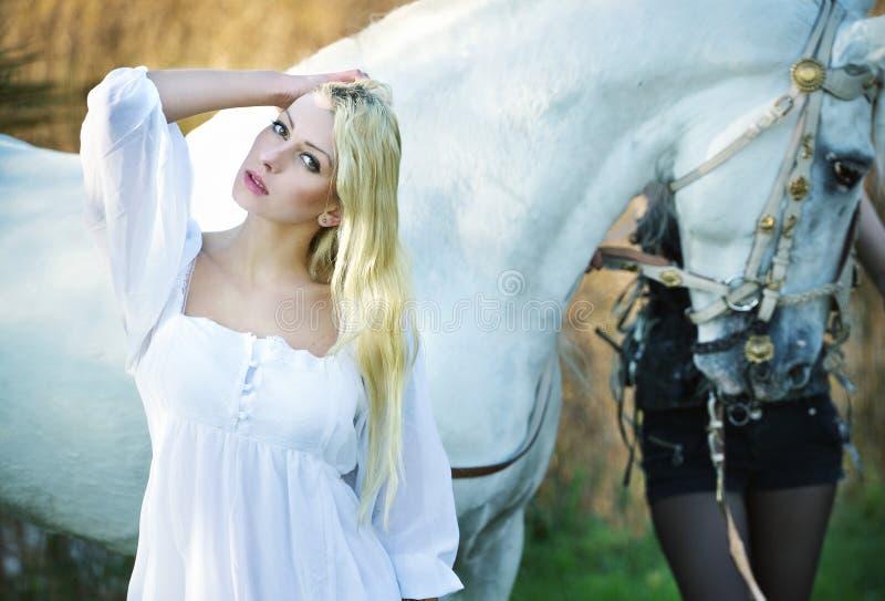 Angelo bianco ed il cavallo nei precedenti immagini stock