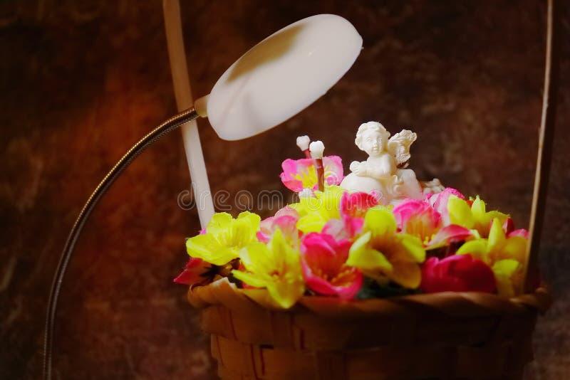 Angelo bianco su un cuore in un mazzo dei fiori artificiali in un canestro fotografia stock libera da diritti