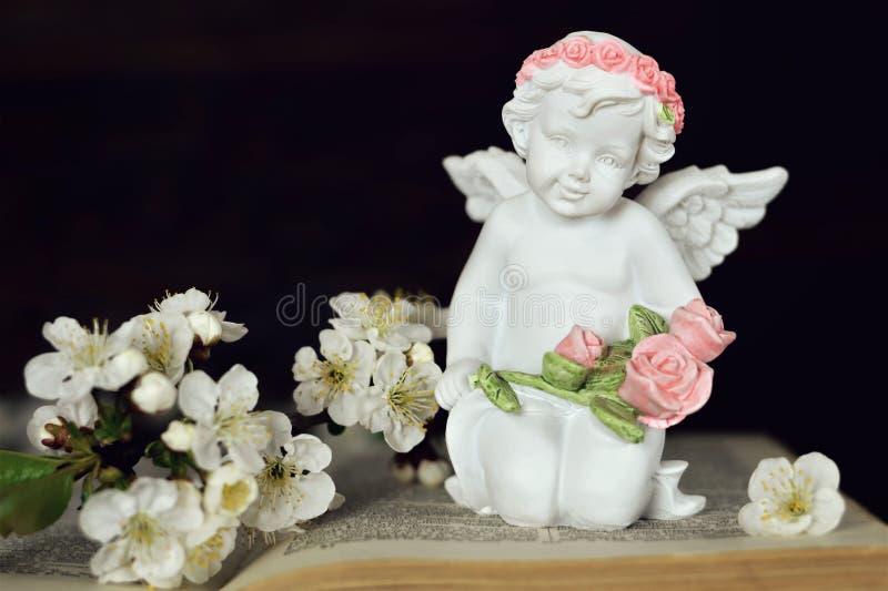 Angelo che si inginocchia sul libro aperto e che tiene i fiori fotografie stock libere da diritti
