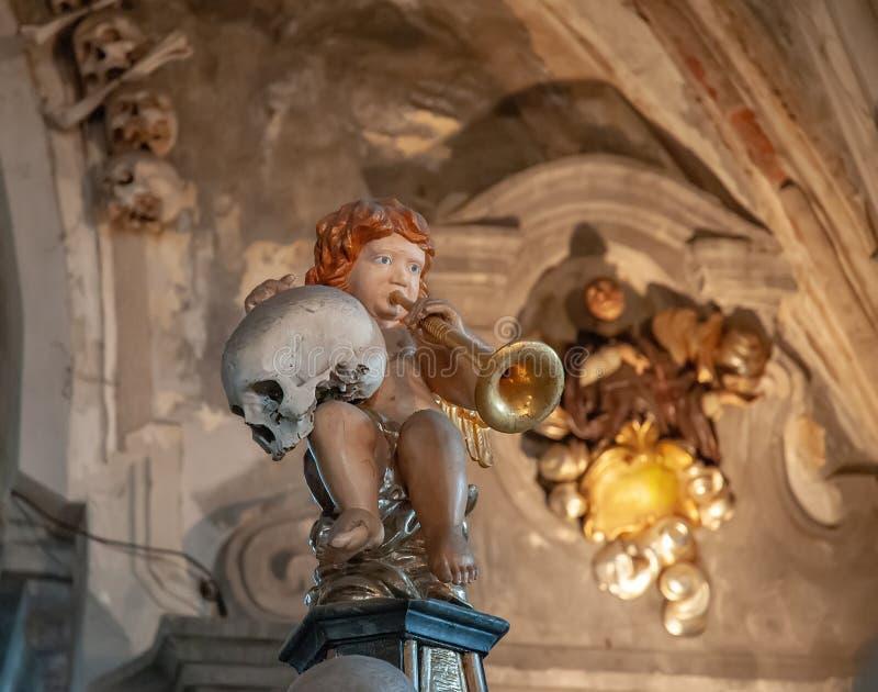 Angelo che tiene un cranio e una tromba umani su una decorazione nell'ossario di Sedlec, Kutna Hora, repubblica Ceca fotografia stock libera da diritti
