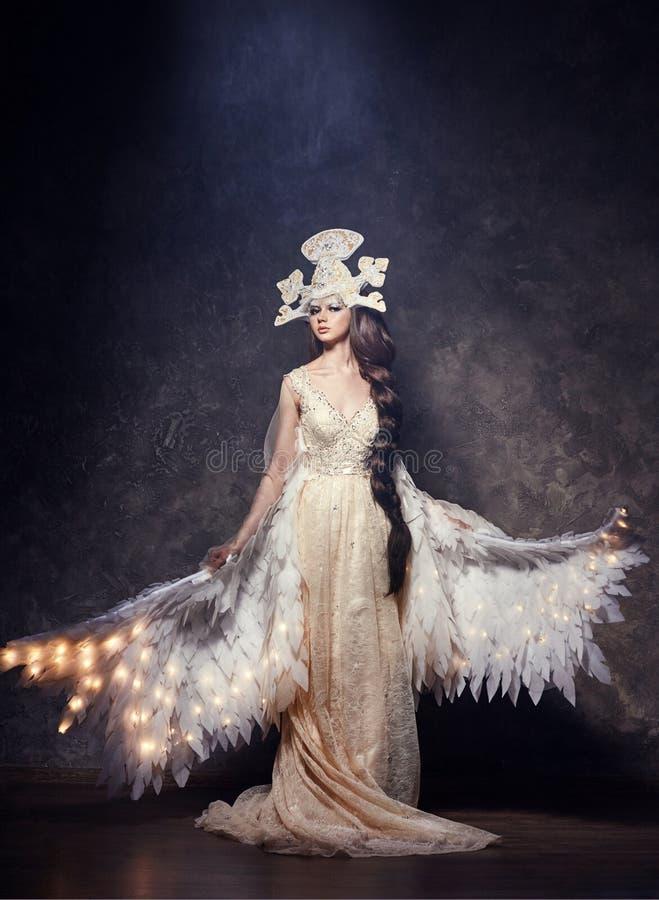 Angelo di Art Woman con le ali in vestito lungo lussuoso e casco favoloso Uccello della ragazza con le ali luminose che posano su immagini stock