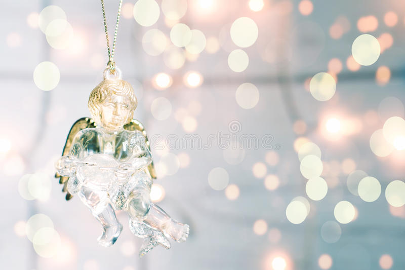 Angelo di vetro di Natale del giocattolo su un fondo del bokeh di golgen immagine stock