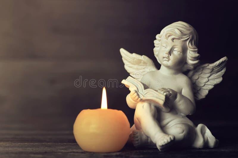 Angelo e candela bianca su fondo scuro Angelo custode che legge un libro fotografie stock