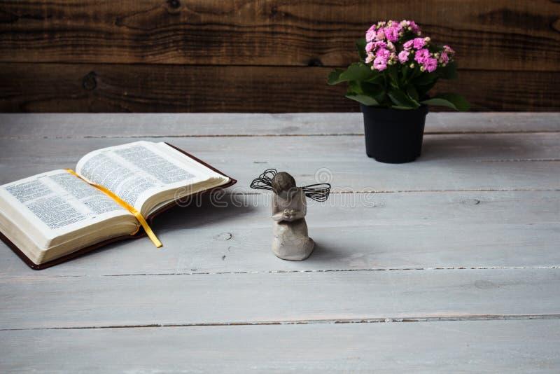 Angelo e la bibbia ed i fiori aperti fotografie stock