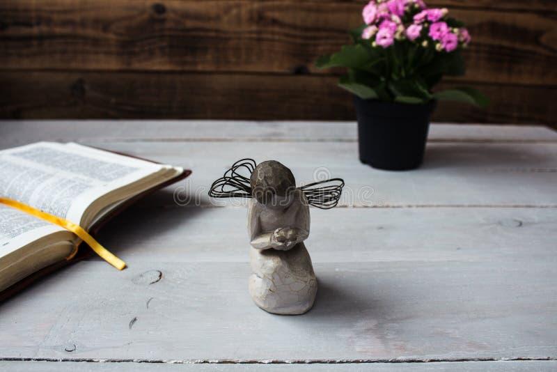 Angelo e la bibbia ed i fiori aperti fotografia stock