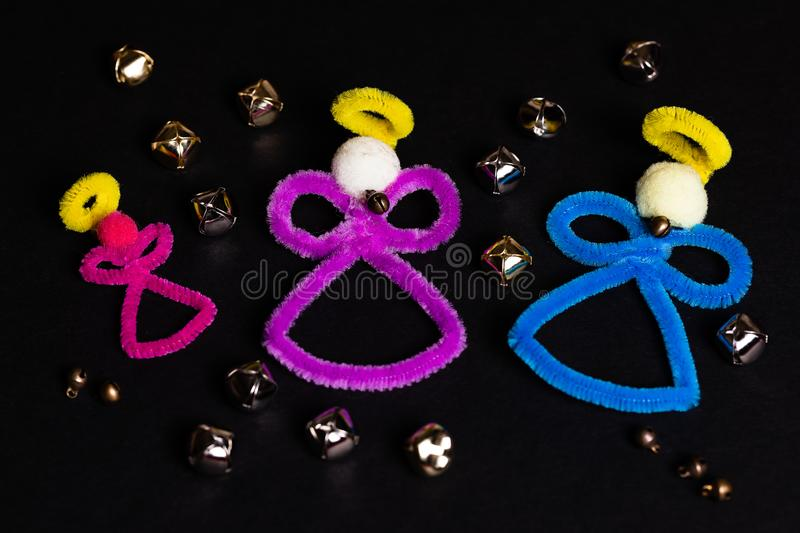 Angels and bells, how an angel gets their wings. 3 pipe-cleaner craft angels on a black background with several gold and chrome stock photography