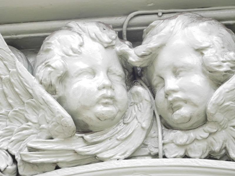 Angels. Close-up of two white cherubic faces of angels on the exterior of very old Fortnum and Mason building that sells tea stock image