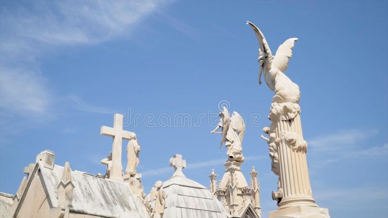 Angels and crosses on grave monuments in cemetery. Action. White stone sculptures and crosses tower on background of stock photography