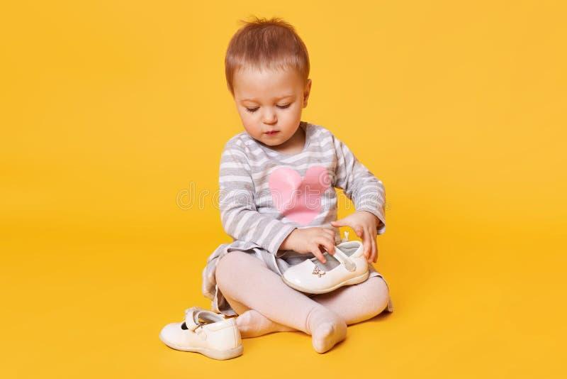 Angemessenes behaartes hübsches kleines Kind, welches das abgestreifte Kleid mit Herzhaltungen lokalisiert über hellem gelbem H lizenzfreie stockfotos