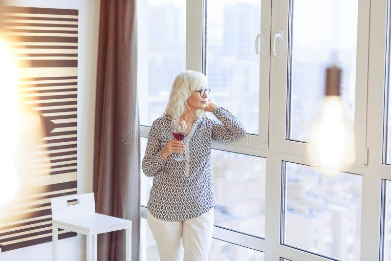 Angenäm åldrig kvinna som bara hemma kopplar av royaltyfria bilder