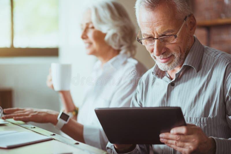 Angenäm åldrig man som använder minnestavlan fotografering för bildbyråer