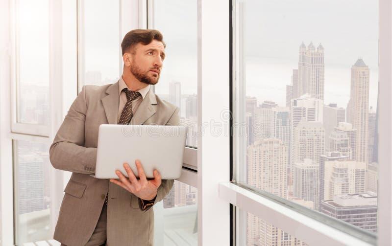 Angenäm affärsman som står det near fönstret i hans kontor royaltyfri fotografi