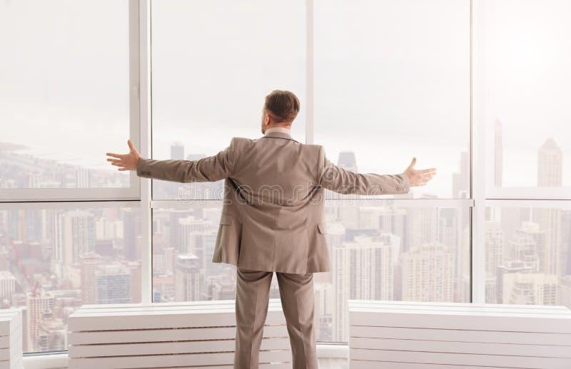 Angenäm affärsman som tycker om sikten från hans kontor royaltyfria bilder