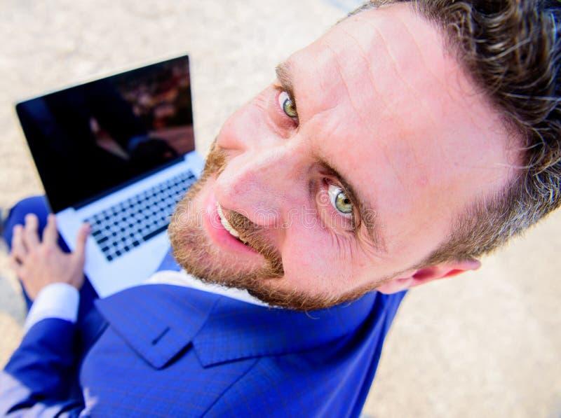 Angenäm arbetsdag utomhus Formella dräktblickar för affärsman tillbaka, medan håll öppnar skärmbärbara datorn Man som ler den gla royaltyfria bilder