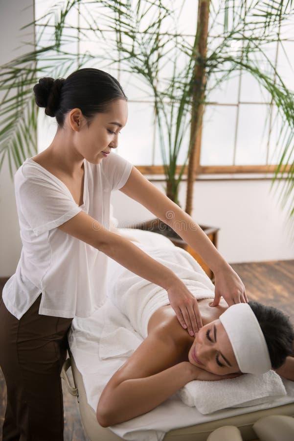 Angenäm asiatisk kvinna som gör en tillbaka massage arkivbild