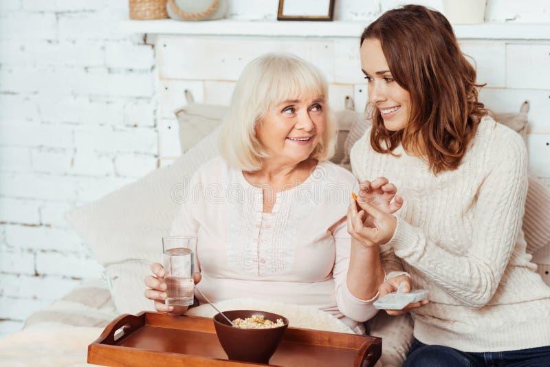 Angenäm att bry sig kvinna som ger preventivpilleren till hennes farmor royaltyfria bilder