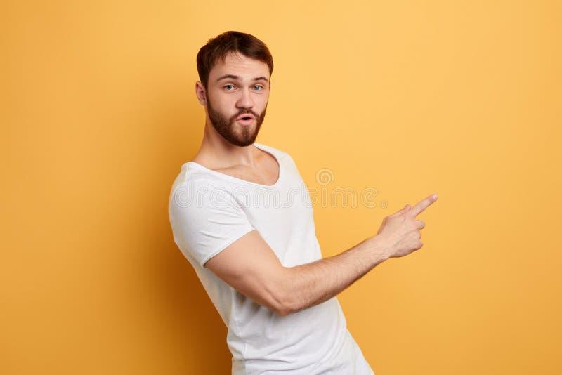 Angenäm attraktiv ung man i vitt T-skitit peka på kopieringsutrymme arkivbilder