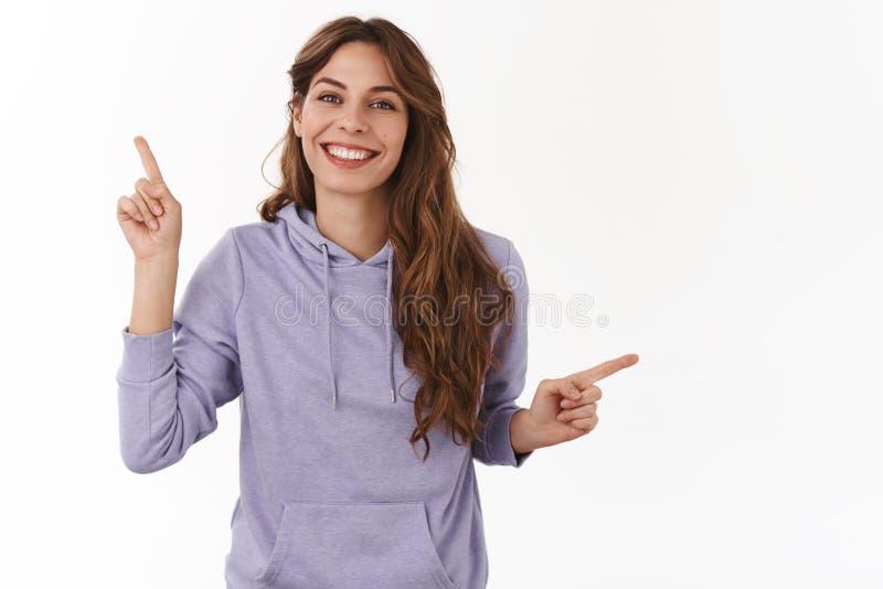 Angenäm bekymmerslös europeisk hipsterflicka som bär den purpurfärgade hoodien som rätt pekar upp från sidan för att främja att l royaltyfri bild