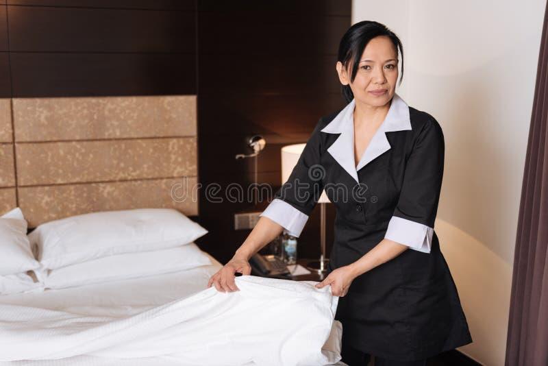 Angenäm bra seende kvinna som gör rumservicen royaltyfri fotografi
