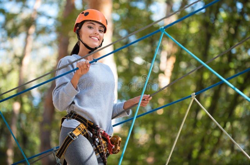 Angenäm bra seende kvinna som tar nöje i klättringaktiviteter arkivfoto