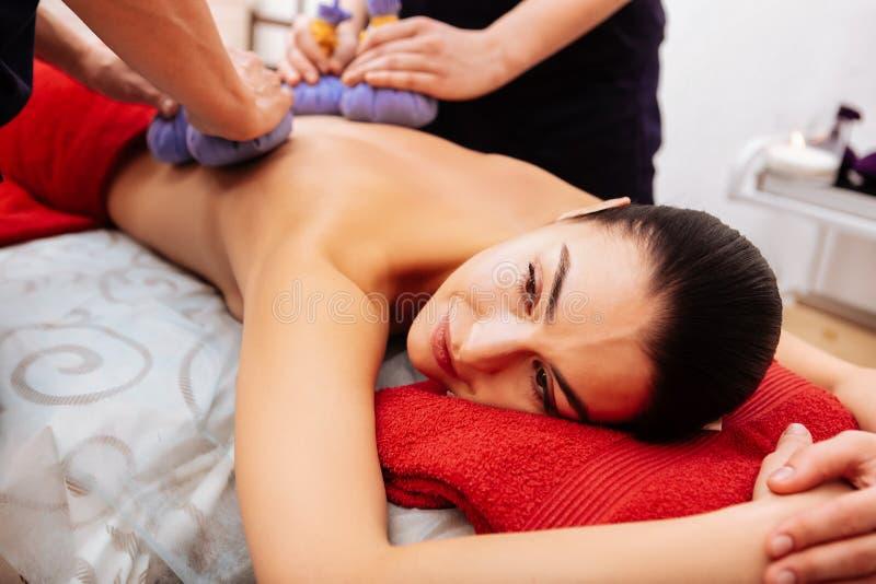 Angenäm delvis-naken kvinna som ligger på magen under att koppla av period royaltyfria foton