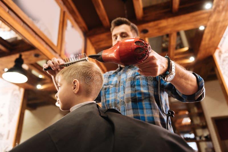 Angenäm erfaren frisör som rymmer en hårtork royaltyfri foto