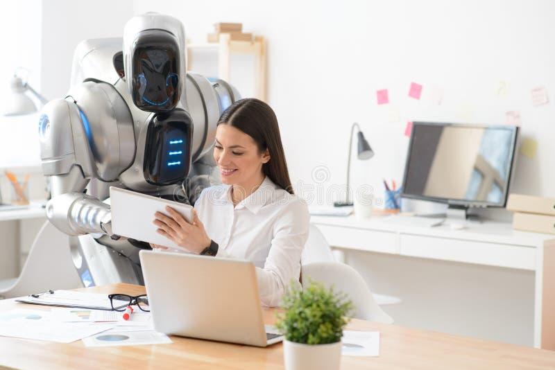 Angenäm flicka och robot genom att använda minnestavlan arkivfoton