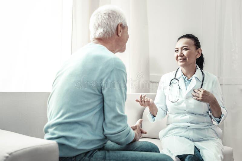 Angenäm glad doktor som ser patienten som talar till honom royaltyfri fotografi