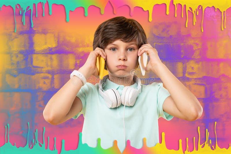 Angenäm glad pojke som bedrar med två telefoner royaltyfri bild