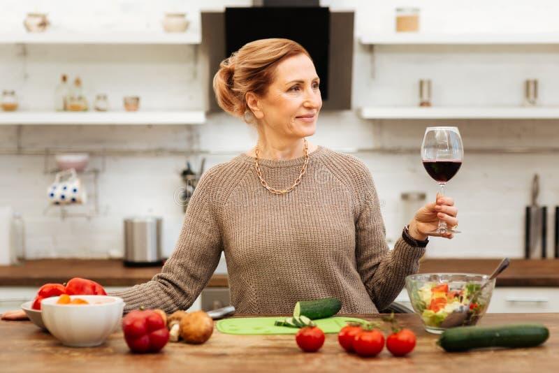 Angenäm härlig dam som spenderar tid i kök och dricker vin royaltyfri fotografi