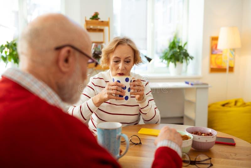 Angenäm hög kvinna som rymmer en kopp med läckert te royaltyfri foto