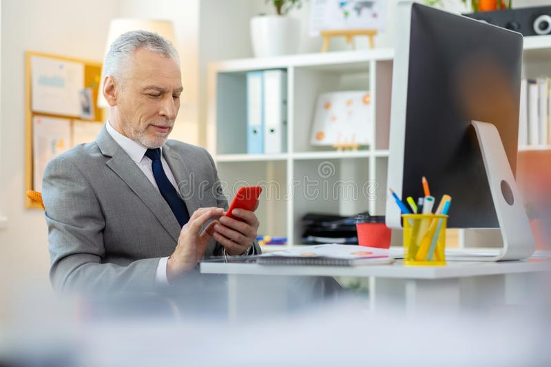 Angenäm intresserad grå färg-haired arbetare som kontrollerar hans sociala massmedia arkivbilder