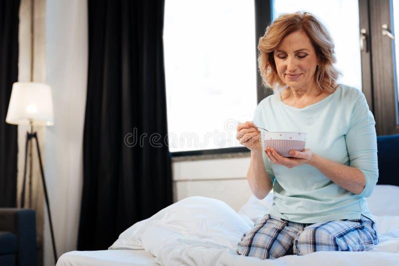 Angenäm kort-haired mogen dam som sitter i säng med bunken av den ljusa frukosten arkivbilder