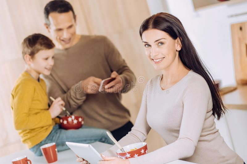 Angenäm kvinna som använder minnestavlan, medan ha frukosten arkivbilder