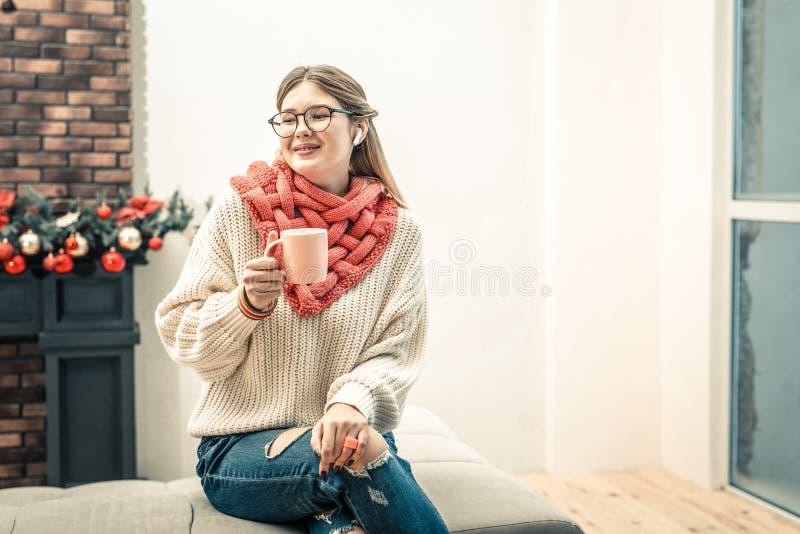 Angenäm kvinna som sitter med korsade ben och dricker varmt kaffe royaltyfri fotografi