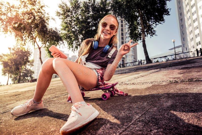 Angenäm långhårig tonåring som visar fredgest, medan sitta i solljus royaltyfri foto